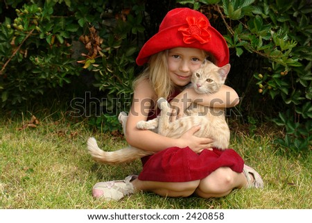 the girl in red hat with a cat - stock photo