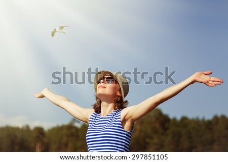 The girl in sunglasses and a hat pulled his hands to heaven. - stock photo