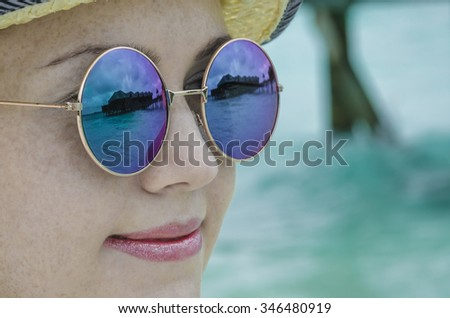 The girl in sunglasses with reflection in them water bungalows