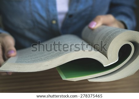 The girl in the blue denim shirt sitting at the table reading a paperback book. Vintage photo. Closeup. - stock photo