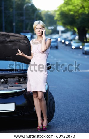 The girl in the broken car on the phone - stock photo