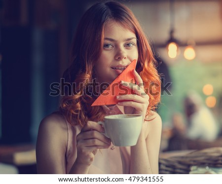the girl in the cafe, a beautiful young woman in the restaurant, wipes his mouth with a napkin