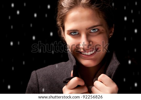 The girl in the coat on a black background - stock photo