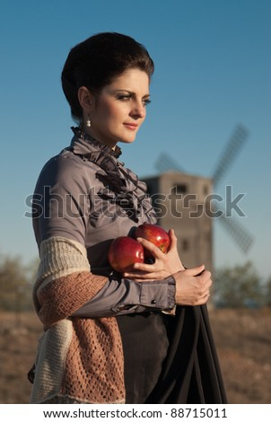 The girl in the costume of the 19th century with apples in their hands against the mill.