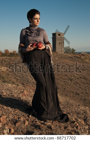 The girl in the costume of the 19th century with apples in their hands against the mill. - stock photo