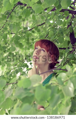 The girl in the foliage of a tree