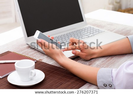The girl in the hands holding a mobile phone. Laptop with blank notepad and pencil with sheets paper on new wooden table. View from the side to workplace writer. - stock photo