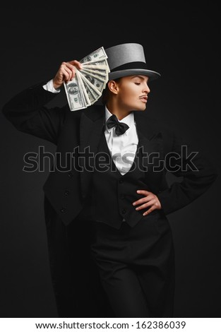 The girl in the image of the gangster with dollars in their hands, on the black background. Woman in men's clothing and a hat with a bundle money in his hand.