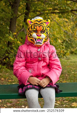 The girl in the mask predatory tiger sitting on a bench in autumn Park - stock photo