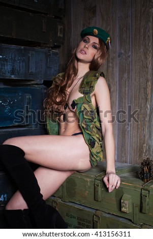 The girl in the military vest. Sexy girl soldier. Military photoshoot. Topless model in the army. Girl with obnozhennoy feeding. Military theme. Army shop. - stock photo