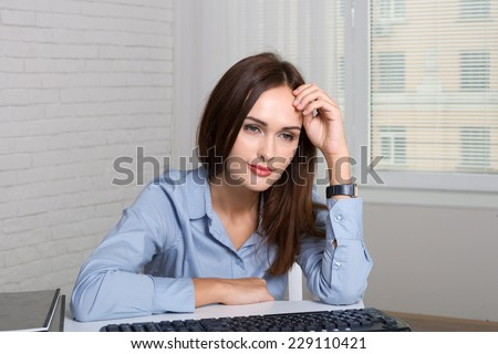 The girl in the office was tired from work and sits propped her hand to head - stock photo