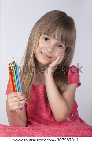 The girl in the pink dress with colored pencils - stock photo