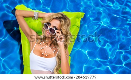 The girl in the pool on a mattress - stock photo