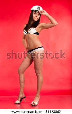 The girl in the sexual form of the sea pirate lingerie on a red background. Full length - stock photo