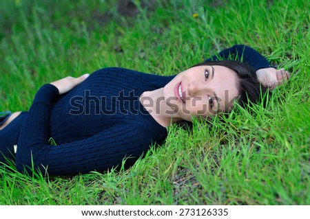The girl in the spring forest lies on the grass