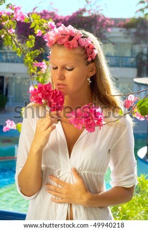 The girl inhaled the fragrance of flowers - stock photo