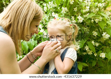 The girl is allergic to pollen. Mom wiped her nose with a serviette - stock photo