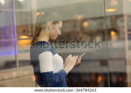 The girl is behind the glass with phone in a cafe