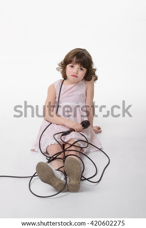 The girl is braided by the cable of the microphone so that is why she is sad. Little lady seems to start crying. Small kid sits on the white ground in studio.