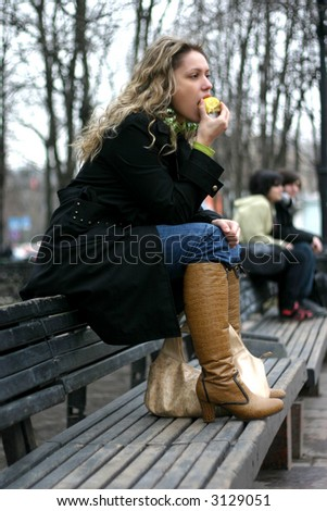 The girl is dressed in a black raincoat eats an apple