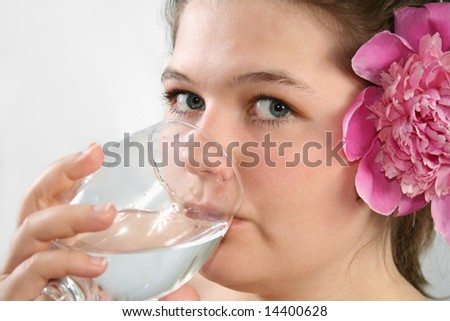 The girl is drincking water from glas.