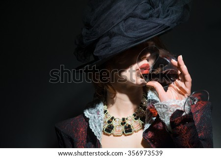 The girl is drinking red wine - stock photo