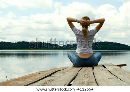 The girl is engaged in meditation on coast of lake - stock photo