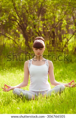 The girl is engaged in yoga on the grass
