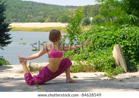 The girl is engaged in yoga on the nature - stock photo
