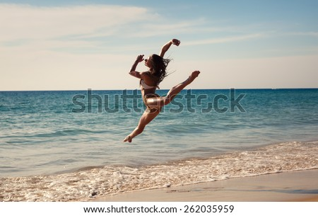 The girl is happy dances at sunset on the seashore