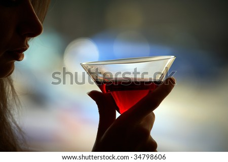 The girl is holding in his hand a glass of alcoholic beverage - stock photo