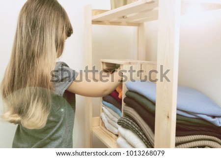 The girl is measuring her mother's clothes. Order in the closet. Smart storage system. Capsule wardrobe. The girl plays and puts mother's clothes in order or chaos. Wardrobe order.
