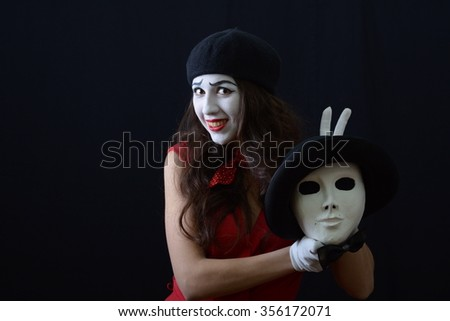 the girl is MIME in a beret and red dress holding a theatrical mask
