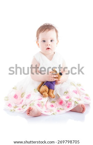 The girl is one year in dress sitting on a white background. - stock photo