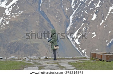 The girl is photographing mountains, Georgia - stock photo