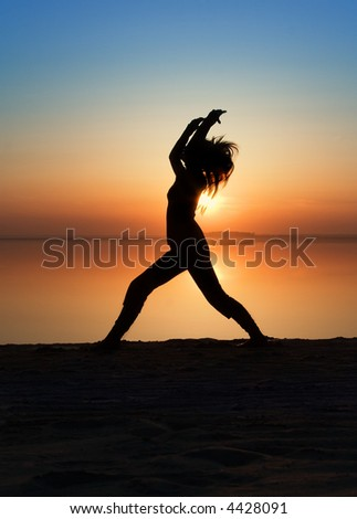 The girl is practising yoga on a coast of a gulf.