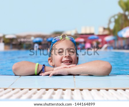 the girl is resting after a swim in the pool - stock photo