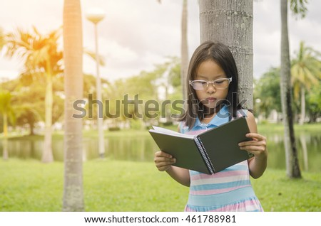 The girl is serious reading under the tree in the park. In the morning and have sunrise