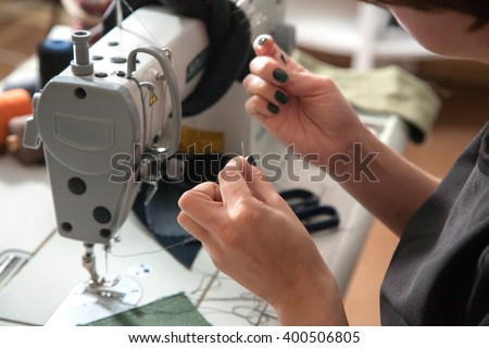 the girl is sewing on the sewing machine in the studio - stock photo