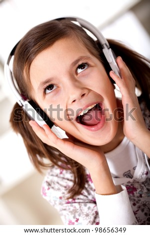 the girl is singing loudly in the headphones