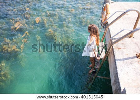 The girl jumps from a pier in water, the long-haired beautiful girl in a white dress,