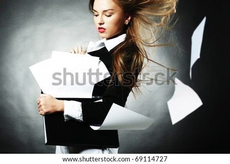 The Girl keeps papers batch on her hands. The Wind raises skyward papers - stock photo
