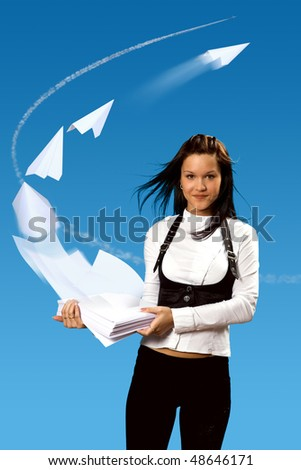 The Girl keeps papers batch on her hands. The Wind raises skyward papers and they fold up in  paper airplanes. - stock photo