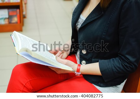 The girl keeps the book in bookstore. The girl's hands with the book. Reading book. - stock photo
