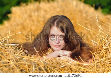 The girl lay on a haystack - stock photo