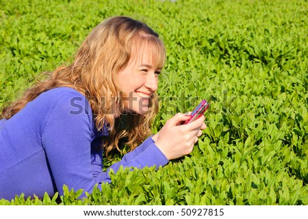 The girl lays on a green grass and reads sms - stock photo