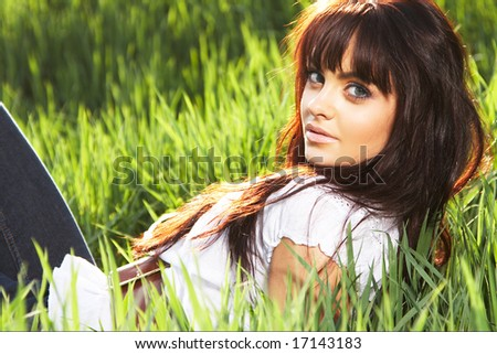 The girl lays on a long green grass - stock photo