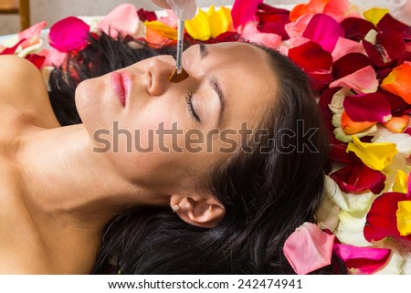 The girl lays on petals in spa salon. Brunette relaxed and waiting for the beginning of the spa treatments. Application of peeling on the girl's face. Facial treatment, rejuvenation, facial. - stock photo
