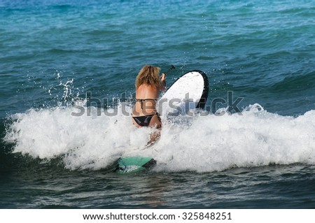 The girl learns to swim on the board with a paddle and overcome the waves of the sea - stock photo