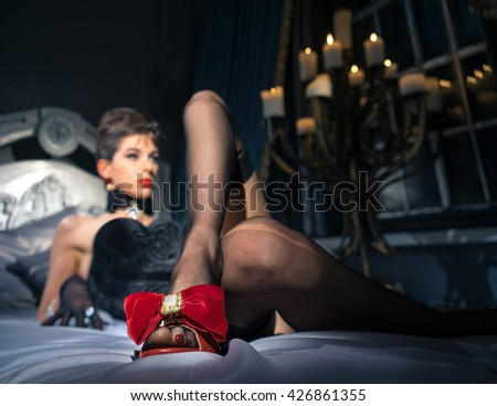 The girl lies on a bed in beautiful red sandals with bows